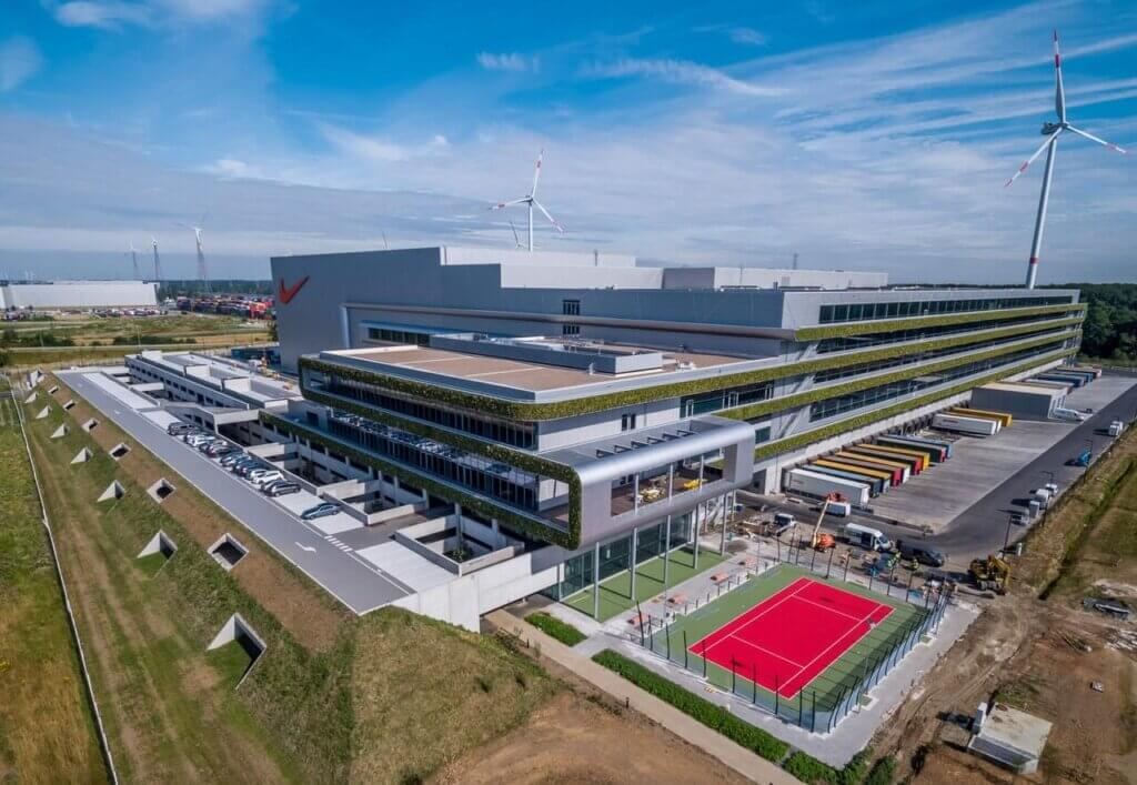 Image of the Nike European Logistics Center. The focus on the picture is sustainability: there is a lot of green space shownon the building, as well as solar panels and wind energy. The logistics service provider trucks are shown on the right side of the picture. The warehouse has very modern architecture.